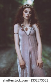 Portrait of a enigmatic beautiful girl posing in a forest. Beauty, fashion. Cosmetics and makeup.