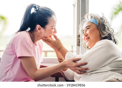 Portrait of enjoy happy love asian family senior mature mother and young daughter smiling laughing embracing and having fun hug together in moments good time at home