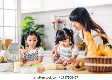 Portrait of enjoy happy love asian family mother and little toddler asian girl daughter child having fun cooking together with baking cookie and cake ingredient on table in kitchen