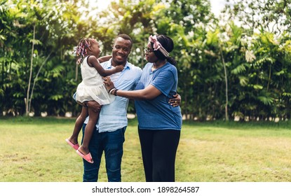 Portrait of enjoy happy love black family african american father and mother with little african girl child smiling and play having fun moments good time in summer park at home