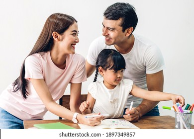 Portrait enjoy happy smiling love asian family father and mother with little asian girl learning and writing in book with pencil making homework at home.Education concept