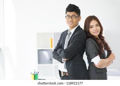 Portrait of an enthusiastic business duo standing back to back