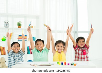 Portrait of enthusiastic pupils holding colorful pencils high in their hands