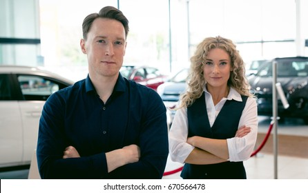 Portrait of entrepreneurs with arms c5rossed standing in car showroom