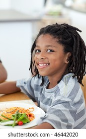 Portrait of ethnic little boy dining in the kitchen