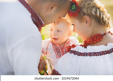 Portrait of ethnic ukrainian family wearing traditional white clothes. Father, mother and little baby having fun outside at summer sunny field. Horizontal color photography.