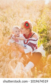 Portrait of ethnic ukrainian family wearing traditional white clothes. Young mother and little baby having fun outside at summer sunny wheat field. Vertical color photography.