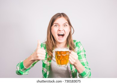 Portrait an euphoric sports fan holding a mug of beer. Woman with beer