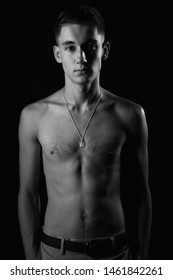 portrait of a european boy with weak body naked on the top, against a black background, black and white, Chisinau, Moldova