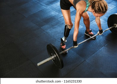 Portrait of european disabled woman wearing prosthesis in tracksuit training and lifting barbell in gym