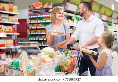 Portrait of european family standing with full cart in supermarket