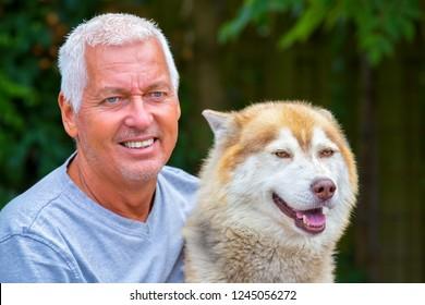 Portrait of european man with adult husky dog