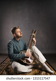 Portrait of a European man playing the sitar sitting on the carpet- Image