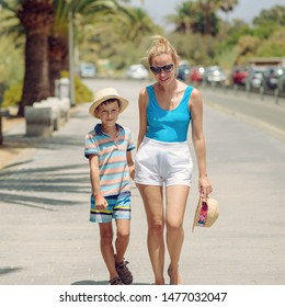 Portrait of European mother and son with sunhats holding hands and walking by sidewalk.