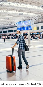 Portrait of European nerd man in glasses and plaid shirt with luggage. tourist boarding plane taking a flight close to the gate wearing face mask. Coronavirus flu virus travel