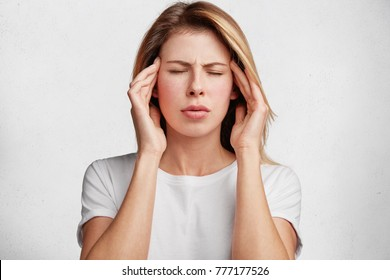 Portrait of European woman has headache, keeps hands on temple, closes eyes, dressed casually, isolated over white concrete wall. Desperate frustrated female has troubles, concentrates on solution