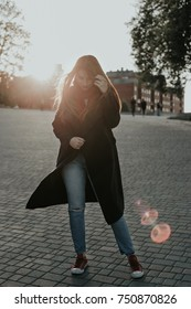 Portrait of european woman on sunset. Model posing at camera on city street. Girl dressed in black coat, jeans and red scarf. Woman looking down. Autumn.