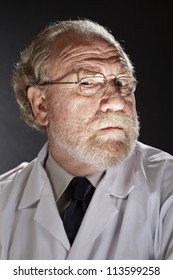 Portrait of evil doctor in lab coat and necktie with sinister expression. Dark background and dramatic low angle spot lighting create spooky shadows on face.