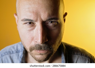 Portrait of an evil man, with orange background.