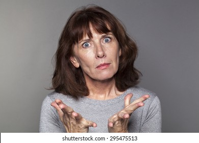 portrait of exasperated 50's woman losing faith with palm hands opened for anger
