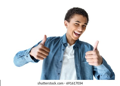 portrait of excited african american teenager showing thumbs up isolated on white