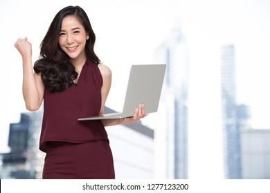 Portrait of an excited Asian woman holding laptop computer and celebrating success over building background, Raising arms with a look of happiness, Female model