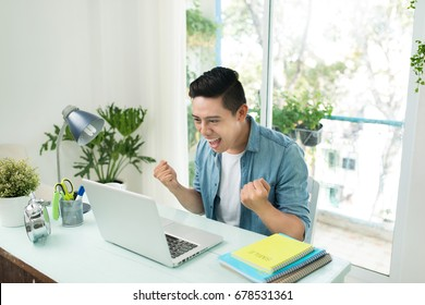 Portrait of excited asian young man working on laptop computer at desk