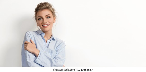 Portrait of excited attractive young woman happily smiling and posing indoors. Light-haired model with kind eyes and natural beauty. Sweet girl on white background