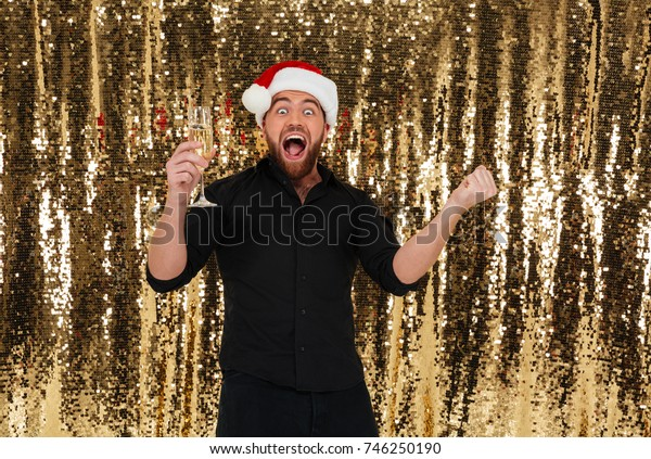 Portrait of an excited bearded man in christmas hat celebrating and drinking champagne from a glass isolated over golden shiny bakground