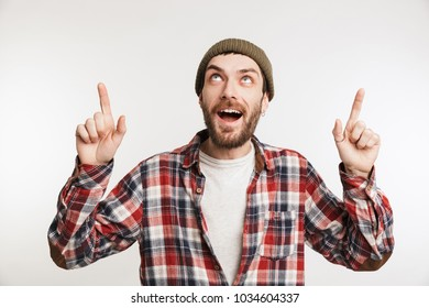 Portrait of an excited bearded man in plaid shirt pointing fingers up isolated over white background