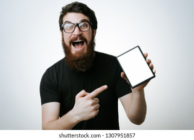 Portrait of a excited bearded man pointing finger on blank tablet computer screen isolated on a white background
