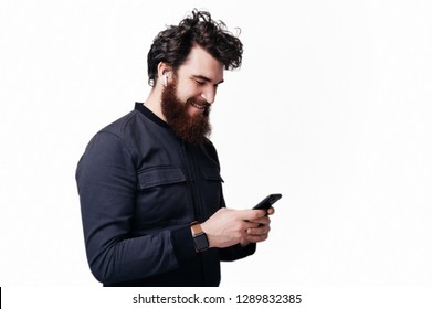 Portrait of excited bearded man using his phone and wearing airpods