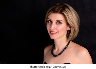 Portrait of an excited beautiful blond woman with bob hairstyle on black background