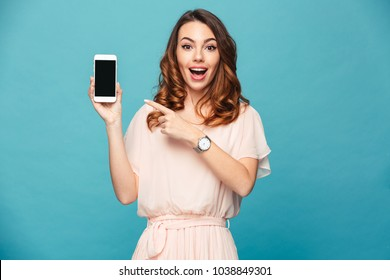 Portrait of an excited beautiful girl wearing dress pointing finger at blank screen mobile phone isolated over blue background