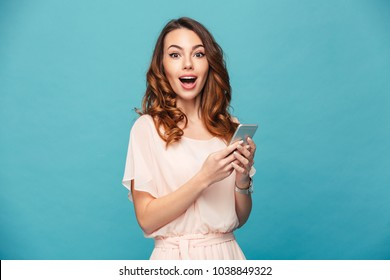 Portrait of an excited beautiful girl wearing dress holding mobile phone isolated over blue background