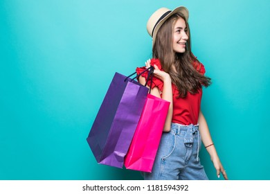 Portrait of an excited beautiful girl wearing dress and sunglasses holding shopping bags isolated over blue background