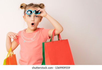 Portrait of an excited beautiful little child girl wearing dress and sunglasses holding shopping bags isolated over light background