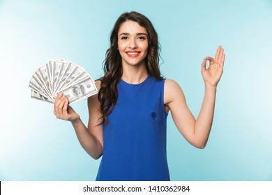 Portrait of an excited beautiful young brunette woman standing isolated over blue background, showing money banknotes, showing ok