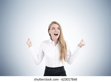 Portrait of an excited blond woman in formal clothes screaming with joy with her hands in the air. Gray background.
