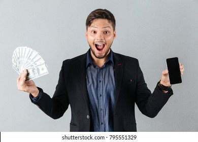 Portrait of an excited businessman holding bunch of money banknotes and showing blank screen mobile phone isolated over gray background