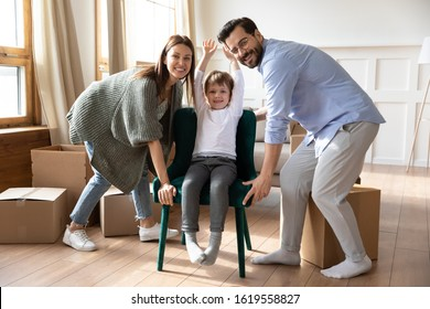 Portrait of excited caucasian young family carry small cute son sit in chair settle in living room in new home, smiling parents have fun unpacking moving relocating to own house with little boy child