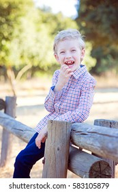 portrait of excited cheerful caucasian boy holding his wobbly tooth
