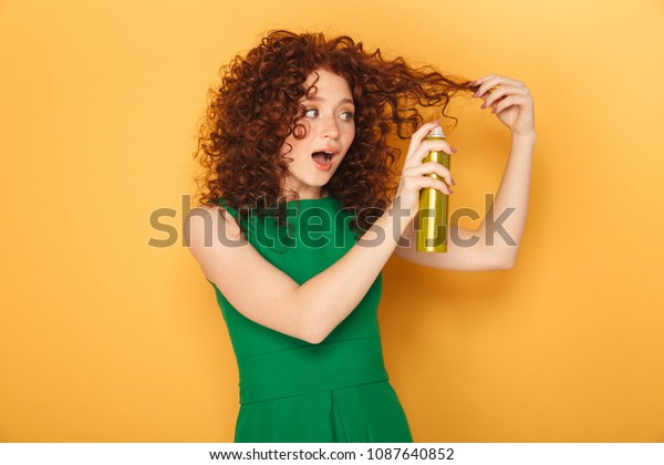 Portrait of an excited curly redhead woman using hair spray isolated over yellow background