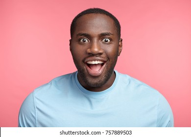 Portrait of excited dark skinned man stares at camera, sees what he likes greatly, has bated breath, wears casual clothes, isolated over pink background. Amazed black male model has stunned expression
