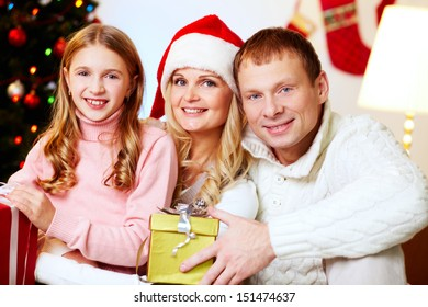 Portrait of an excited family holding Christmas presents
