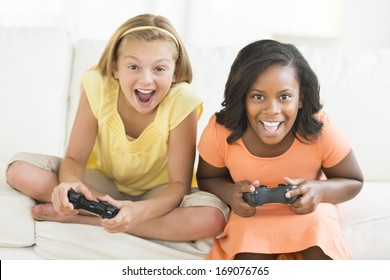 Portrait of excited female friends playing video games at home