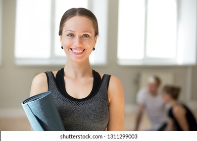 Portrait of excited female yoga teacher posing with fitness mat looking at camera, happy toned fitness instructor or coach in sportswear smiling making picture during training in yoga studio