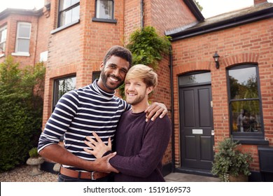 Portrait Of Excited Gay Male Couple Standing Outside New Home On Moving Day Together