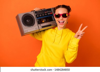 Portrait of  excited girl having top-knot making v-signs holding boombox isolated over orange background
