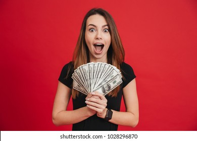 Portrait of an excited girl holding bunch of money banknotes isolated over pink background